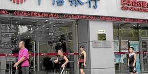 Pedestrians walk past a China CITIC Bank Corp. branch in Shanghai, China, on Tuesday, Aug. 10, 10, 2010. China CITIC Bank Corp. is expected to announce interim results tomorrow. Photographer: Kevin Lee Bloomberg br