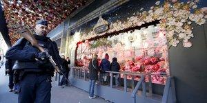 Un policier français patrouille devant les Galeries Lafayette après les attentats de Paris survenus le 13 novembre (photographie prise le 22 novembre devant les grands magasins, shopping)